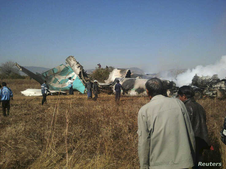 FILE - People gather at the wreckage of a Air Bagan Fokker-100 passenger jet that crashed in Heho, Myanmar, Dec. 25, 2012. Two people were killed and 10 wounded in northeast Myanmar on Tuesday when the passenger plane missed an airport runway in heavy fog and landed in a rice paddy, state television said.  REUTERS/Stringer (MYANMAR - Tags: DISASTER TRANSPORT) - GM1E8CP16WF01