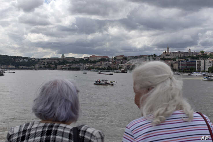 Two women watch a rescue vessel off the Margit bridge on the Danube river where a sightseeing boat had capsized in Budapest, Hungary, May 31, 2019. Hungarian police have detained the captain of a cruise ship that collided with a sightseeing boat packed with South Korean tourists, causing it to sink quickly in the Danube River, as loved ones of the missing and dead were expected to arrive Friday in Budapest. (AP Photo/Marko Drobnjakovic)