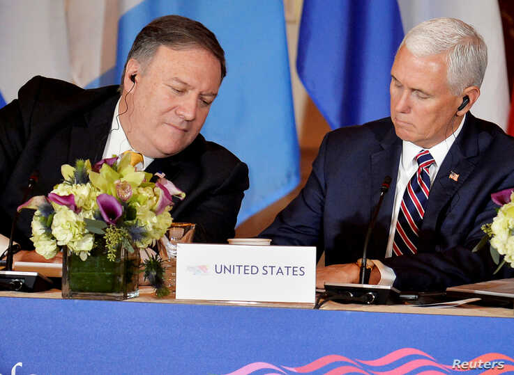 U.S. Secretary of State Mike Pompeo, left, leans in as Vice President Mike Pence makes a note during the Second Conference on Prosperity and Security in Central America, in Washington, Oct. 11, 2018.
