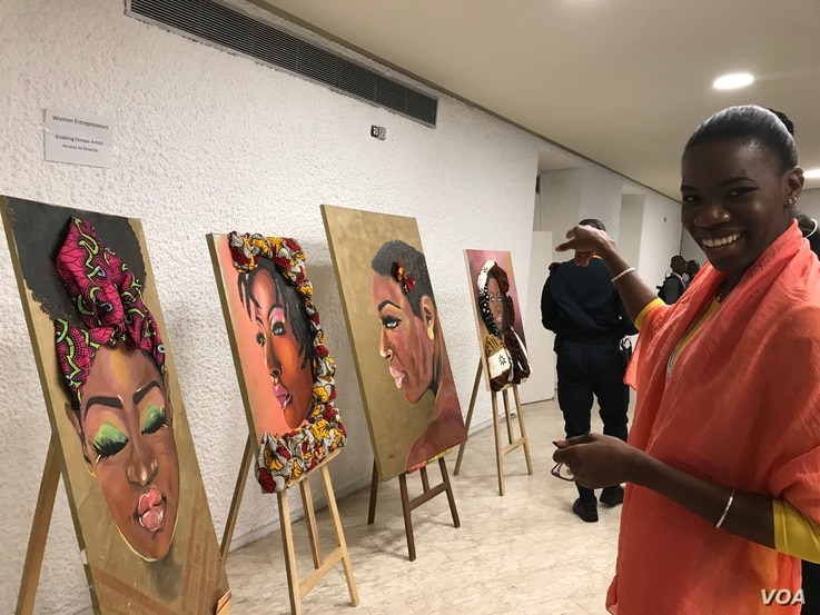 Tatou Dembele, a painter and owner of a food marketing company, points to her favorite of her own paintings. (E. Sarai/VOA)