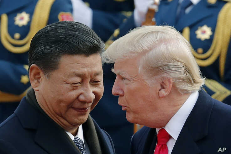 FILE - In this Nov. 9, 2017, file photo, U.S. President Donald Trump, right, chats with Chinese President Xi Jinping during a welcome ceremony at the Great Hall of the People in Beijing. The United States and China are scheduled Thursday, May 9, 2019, to resume talks to try to back off an escalating trade war. (AP Photo/Andy Wong, File)