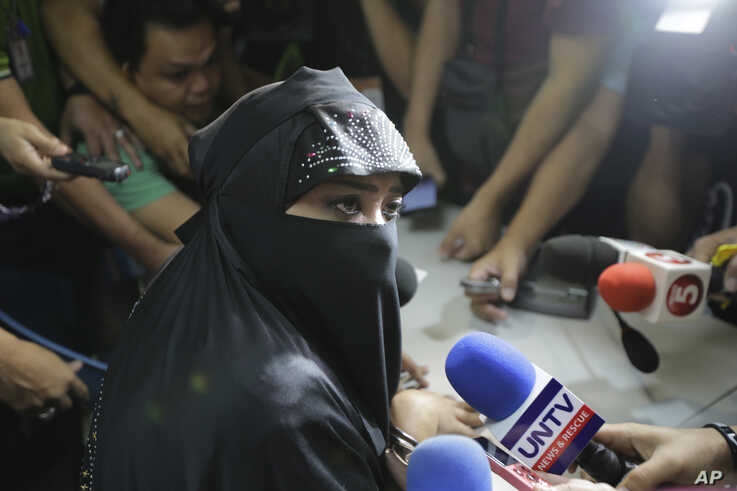 FILE - Karen Aizha Hamidon, who allegedly worked to encourage several Indian militants last year to join the Islamic State group in the Middle East, is surrounded by reporters after attending a hearing at the Department of Justice in Manila, Philippines,