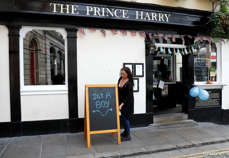 """A sign reading """"It's a boy"""" is pictured a day after Meghan, Duchess of Sussex, gave birth to a baby boy, outside the Prince Harry pub in Windsor, Britain May 7, 2019."""