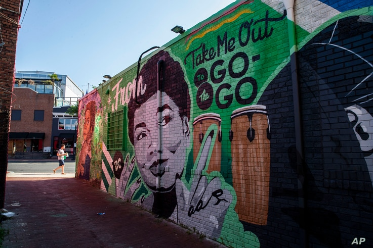 A mural decorates a building behind a Metro PCS store, May 25, 2019 in the Shaw neighborhood of Washington.