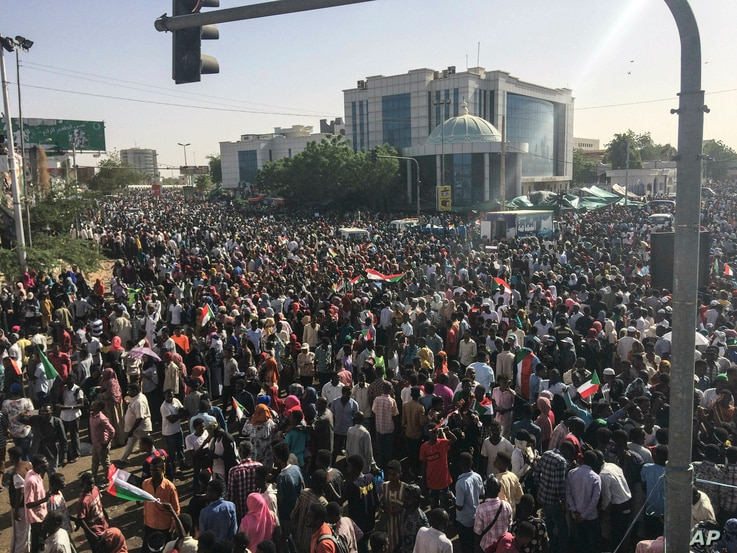 Sudanese demonstrators march with national flags as they gather during a rally demanding a civilian body to lead the transition to democracy, outside the army headquarters in the Sudanese capital Khartoum, April 13, 2019.  (AP Photo)