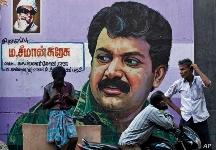 FILE - People stand in front of a mural of Sri Lanka's Liberation Tigers of Tamil Eelam (LTTE) leader Velupillai Prabhakaran painted on a wall in Chennai, India, May 19, 2015. Across Chennai, large billboards with photographs of Prabhakaran, the lead...