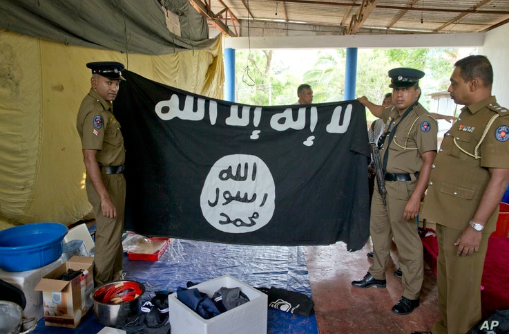 """Police officers display a flag in Arabic that reads: """"There is no god, but Allah"""" and """"Of Allah is the Prophet, Muhammad"""" in Ampara, Sri Lanka, April 28, 2019."""
