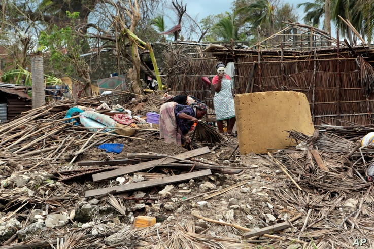 A family picks up a few items from their house, which was damaged by Cyclone Kenneth when it struck Ibo island north of Pemba city in Mozambique, May, 1, 2019. The government has said more than 40 people have died after the cyclone made landfall on T...