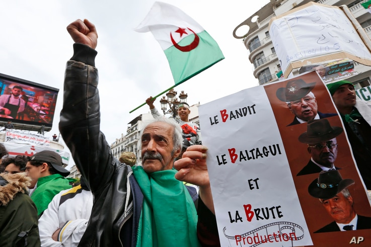 A demonstrator holds a sign referring to the three B's, Abdelkader Bensalah, Tayeb Belaiz et Noureddine Bedoui, interim rulers they want removed from their posts, during a rally in Algiers, Friday April 5, 2019.