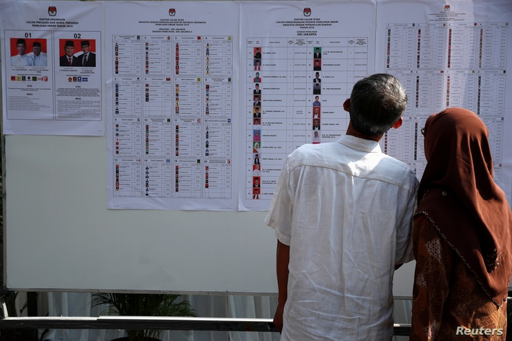 People look at a list of electoral candidates during elections in Jakarta, Indonesia, April 17, 2019.
