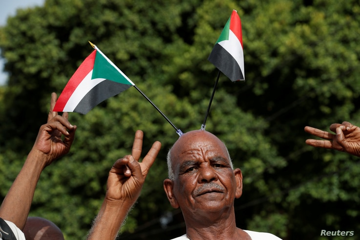 Protesters make victory signs as one of them carry Sudanese flags on his head during a demonstration in front of the Defence Ministry in Khartoum, Sudan, April 18, 2019.