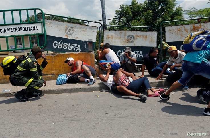 People take cover behind barriers as shots are fired near the Simon Bolivar international bridge, on the border between Colombia and Venezuela, in Cucuta, Colombia, May 3, 2019.