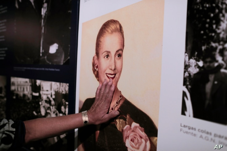 """A woman touches a picture of Eva Peron on display at the home-turned-museum """"Casa Museo Eva Perón"""" in Los Toldos, Argentina, May 6, 2019."""