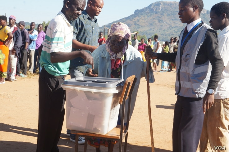 Polling monitors offer assistance as an elderly woman casts her vote in Tuesday's election in Malawi.  (L Masina/VOA)