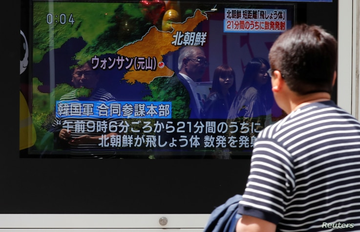 A man watches a television screen showing a news report on North Korea firing several short-range projectiles from its east coast, on a street in Tokyo, May 4, 2019.