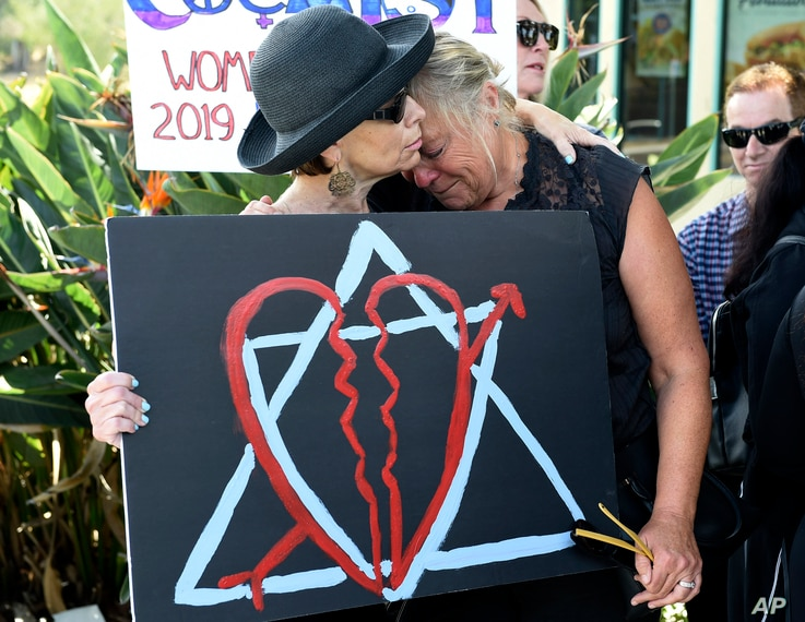 Leslie Gollub, left, and Gretchen Gordon hug at a vigil held to support the victims of Saturday's shooting at Chabad of Poway synagogue, Sunday, April 28, 2019, in Poway, Calif.