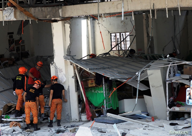 Rescuers are seen at a collapsed four-story building following an earthquake in Porac town, Pampanga province, Philippines, April 23, 2019.