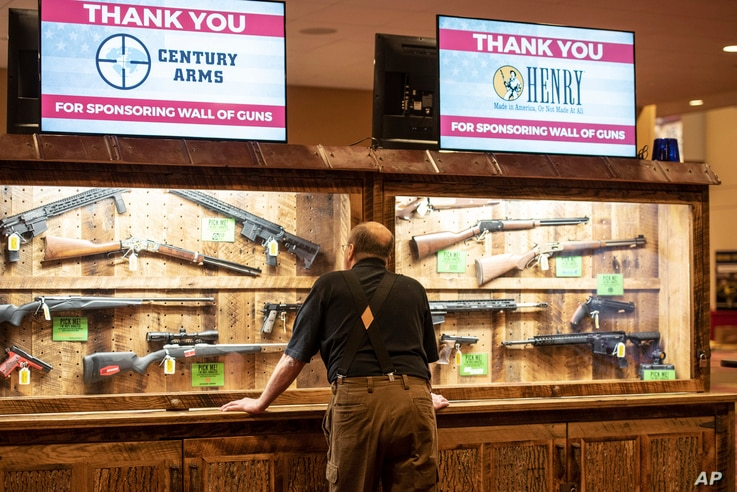 A man looks at cases of firearms in the halls of the Indianapolis Convention Center, April 25, 2019, where members of the National Rifle Association is holding its 148th annual meetings in Indianapolis.