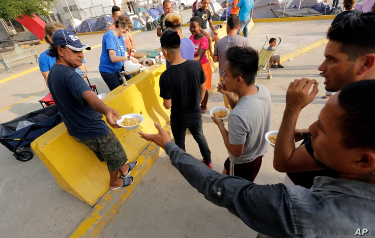 FILE - Migrants seeking asylum in the United States receive breakfast from a group of volunteers near the international bridge, April 30, 2019, in Matamoros, Mexico.