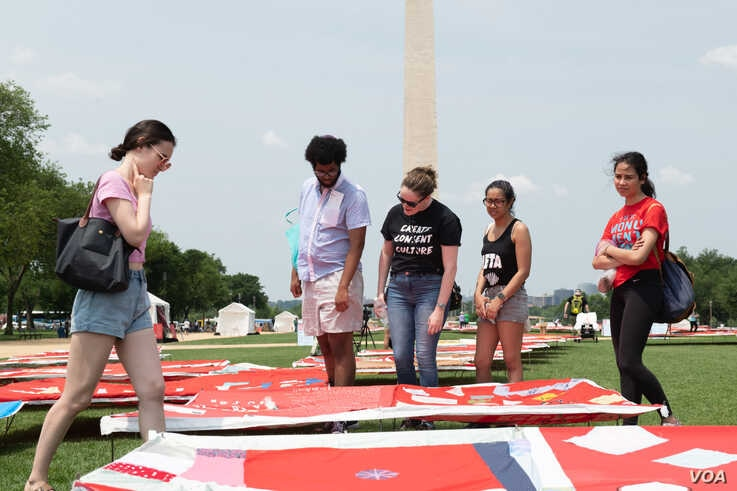Tourists take a closer look at the quilt on display on the National Mall