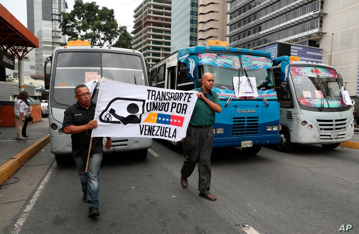 """Transportation union members hold a work stoppage to protest the government of President Nicolas Maduro, a former bus driver, as they carry a sign that reads in Spanish """"Transportation united for Venezuela,"""" in the Altamira neighborhood of Caracas, V..."""
