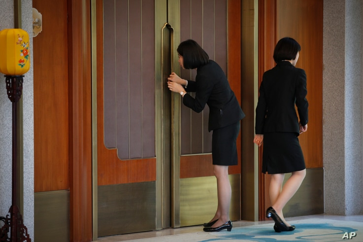 A Chinese staff member tries to sneak a peek inside during a China-U.S. trade meeting at the Diaoyutai State Guesthouse in Beijing, May 1, 2019.