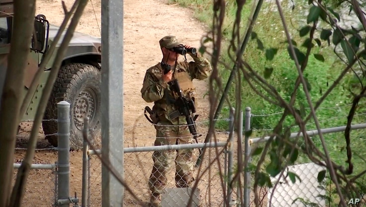 FILE - In this April 10, 2018, file frame from video, a National Guard troop watches over Rio Grande River on the border in Roma, Texas.