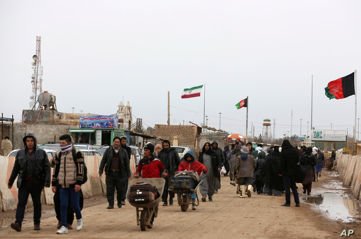 FILE - Afghans return to Afghanistan at the Islam Qala border with Iran, in the western Herat province, Feb. 20, 2019. Security officials worry that Iranian-backed Afghan veterans of the war in Syria will one day become a secret army for Tehran in Af...
