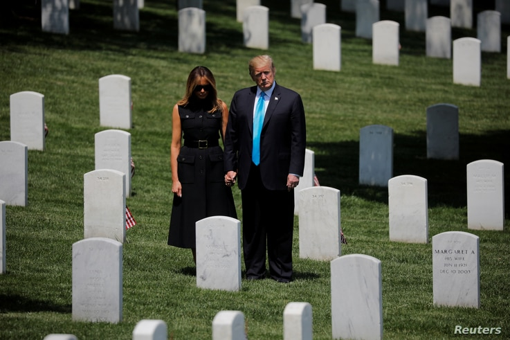 """U.S. President Donald Trump and first lady Melania Trump stand among the graves during the annual """"flags in"""" ceremonies before Memorial Day as the president visits Arlington National Cemetery in Arlington, May 23, 2019."""