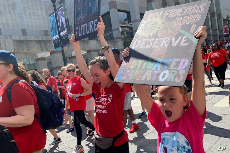 """Zoë Powell, 8, leads a chant of """"Whose school? Our school!"""" alongside of her mother, Sarah Jackson, 24, on May 1, 2019, who is a special education teacher at Green Elementary School in Raleigh, North Carolina."""