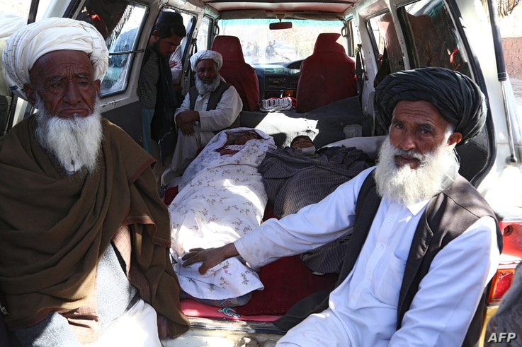 FILE - Afghan men sit next to the bodies of two students who were killed by a Taliban mortar round in a school, in the city of Ghazni, March 30, 2019.