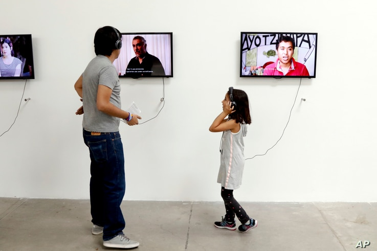 """People listen to video portraits by family members of the 43 college students who went missing in an apparent 2014 massacre at an art exhibit titled """"Reestablish Memories"""" by Chinese concept artist and government critic Ai Weiwei at the Contemporary ..."""