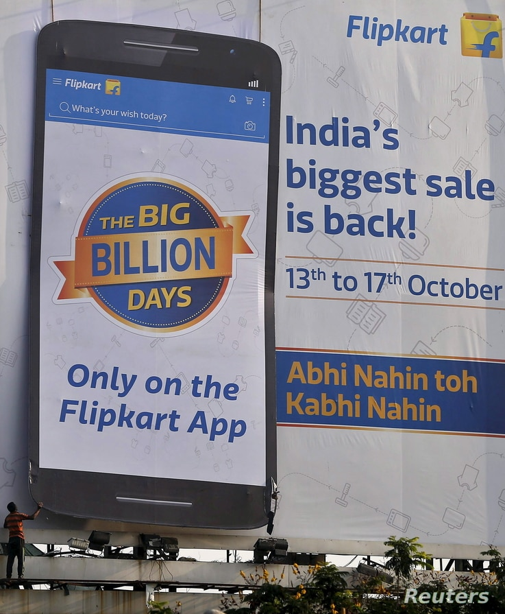 FILE - A worker removes an advertisement billboard of Indian online marketplace Flipkart, installed along the roadside in Mumbai, India, Oct. 16, 2015. Amazon.com Inc. is concentrating on India and its competition, Flipkart.