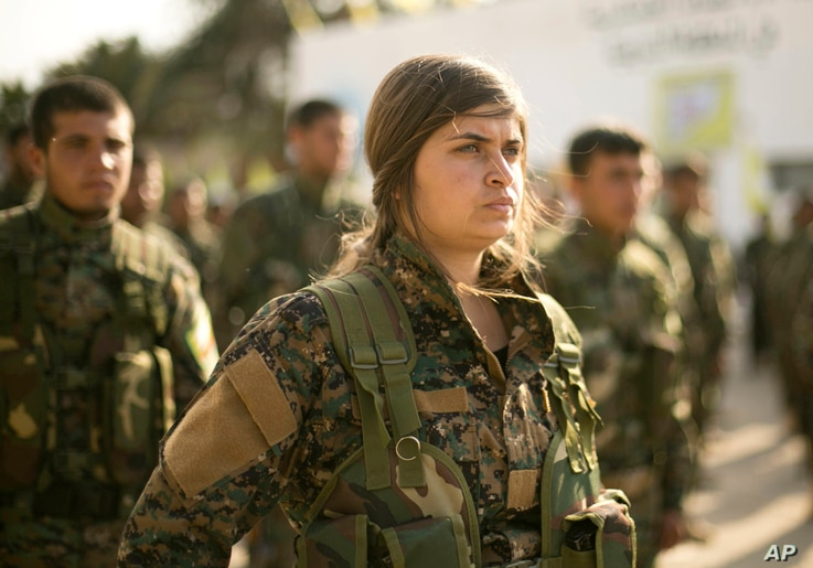 U.S.-backed Syrian Democratic Forces (SDF) stand in formation at a ceremony to mark their defeat of Islamic State militants in Baghouz, at al-Omar Oil Field base, Syria, March 23, 2019.
