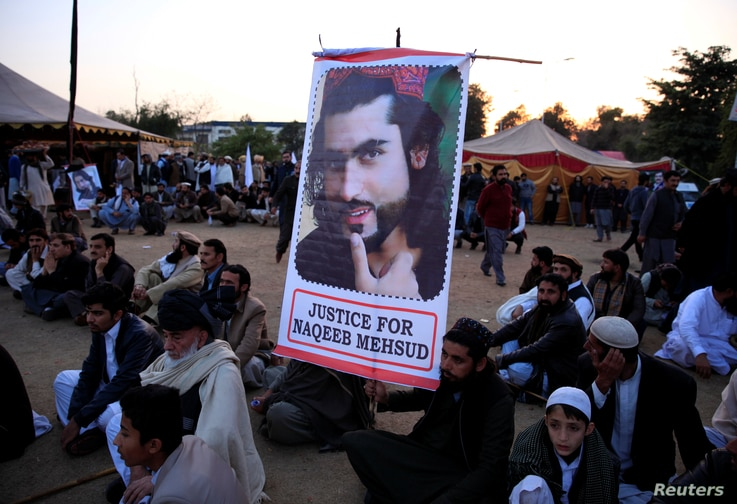 """A member of the Pashtun community holds a picture of Naqibullah Mehsud, whose extrajudicial killing by Karachi police sparked nationwide protests, as he gathers with others to protest against what they say are enforced """"disappearances"""" and routin..."""
