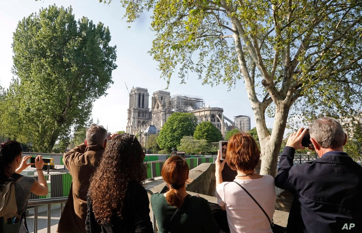 People take pictures of Notre Dame in Paris, April 19, 2019. Rebuilding the 800-year-old cathedral devastated by fire this week will cost billions of dollars as architects, historians and artisans work to preserve the medieval landmark.