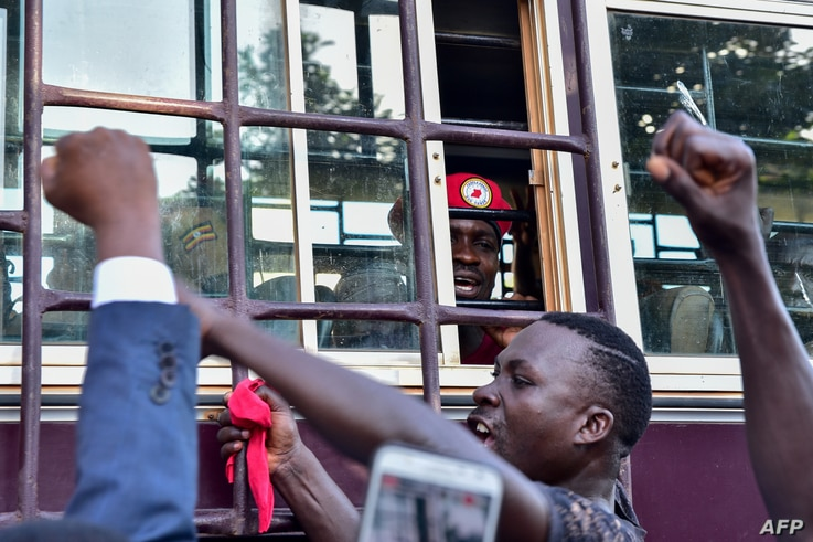 Supporters gather in solidarity with opposition figurehead Robert Kyagulanyi, aka Bobi Wine, gesturing inside the prison bus leading him to Luzira maximum prison in Kampala, April 29, 2019.