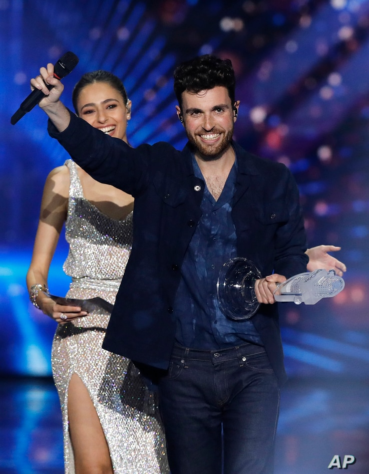 "Duncan Laurence of the Netherlands is watched by presenter Lucy Ayoub, left, as he holds the trophy after winning the 2019 Eurovision Song Contest grand final with the song ""Arcade"" in Tel Aviv, May 18, 2019."