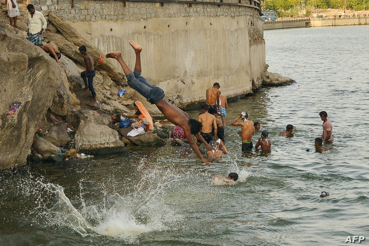 Indian youths cool off in the Ana Sagar lake during a hot day in Ajmer, in Rjasthan state, May 31, 2019. India has been battling a fierce heat wave that has prompted warnings about water shortages and heatstroke.