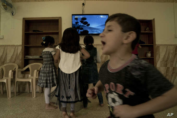 In this Aug. 19, 2018 photo, children watch a cartoon at the state-run al-Zuhour Orphanage, which now hosts children of Islamic State militants, in Baghdad, Iraq. (AP Photo/Maya Alleruzzo)