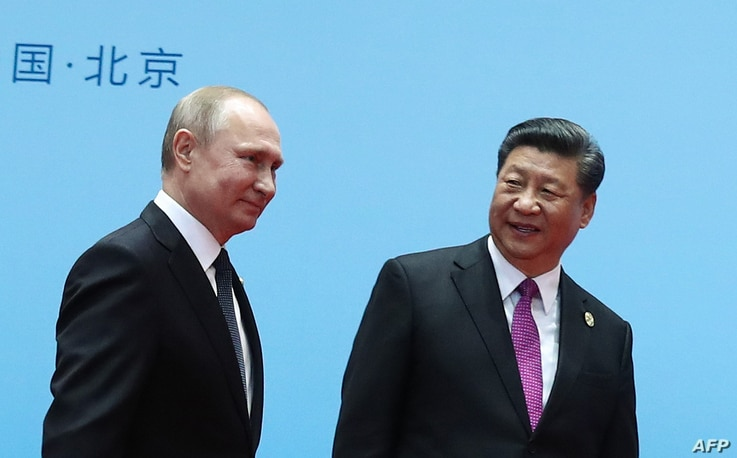 China's President Xi Jinping, right, and Russia's President Vladimir Putin smile during the welcoming ceremony on the final day of the Belt and Road Forum in Beijing, April 27, 2019.