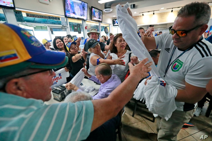 Venezuelans vie for T-shirts as they watch televised news from their country at the El Arepazo Doral Venezuelan restaurant in Doral, Fla., April 30, 2019.