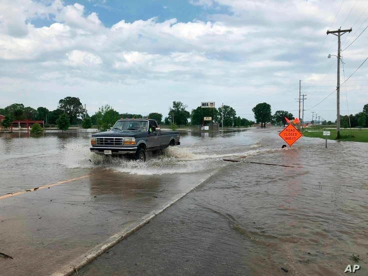 A pickup evacuates from an area in north Jefferson City, Miss., as floodwaters from the Missouri River rise over the road May 24, 2019. The flooding come as residents are still cleaning up from a powerful tornado that hit the state's capital city Wed...