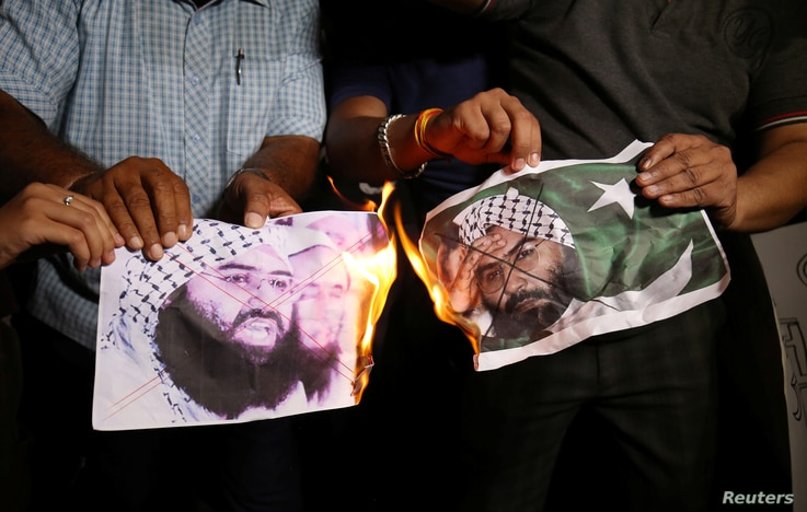 People burn pictures of Masood Azhar, the head of a Pakistan-based militant group Jaish-e-Mohammad, as they celebrate the U.N. Security Council committee's decision to blacklist Azhar, in Ahmedabad, India, May 1, 2019.