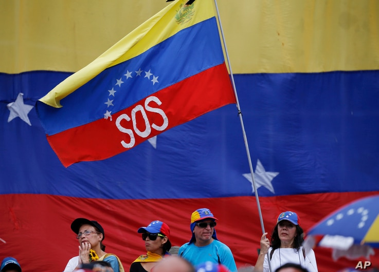 """A supporter of Venezuela's opposition leader and self-proclaimed interim president Juan Guaidó, waves a Venezuelan flag marked with the letters """"SOS"""" during a rally in Caracas, Venezuela, May 11, 2019."""