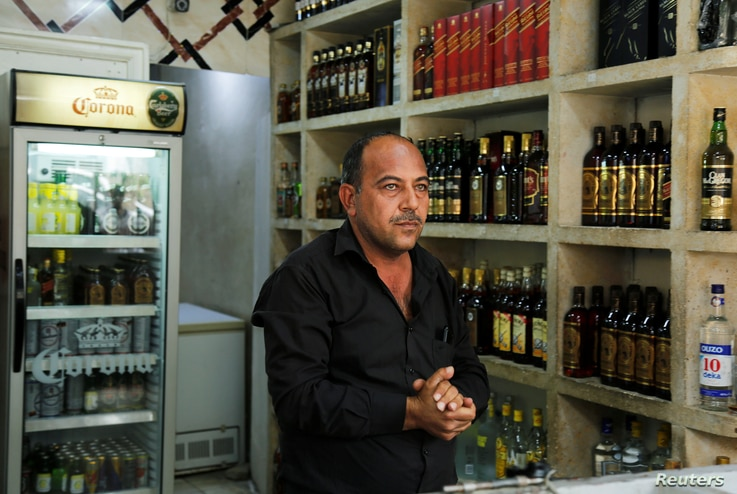 A liquor store owner waits for customers inside his shop, after it was banned during the Islamic State militants' seizure of the city, in Mosul, Iraq, April 18, 2019.