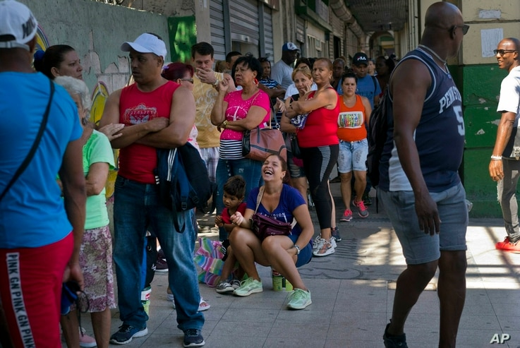 People wait in line to buy chicken at a government-run grocery store in Havana, Cuba, April 17, 2019.
