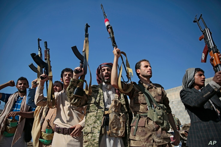 FILE - Tribesmen loyal to Houthi rebels hold up their weapons as they attend a gathering to show their support for the ongoing peace talks being held in Sweden, in Sanaa, Yemen, Dec. 13, 2018.
