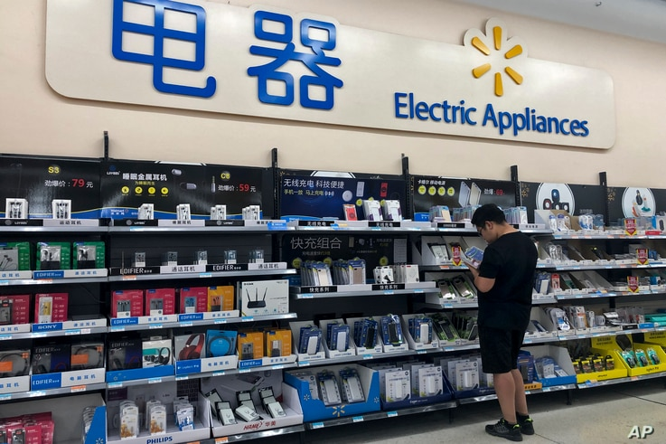 A man looks at digital accessories in Beijing, May 9, 2019. Ratcheting up tension ahead of talks, China vowed Thursday to defend its own interests and retaliate if President Donald Trump goes ahead with more tariff hikes in a dispute over trade and t...