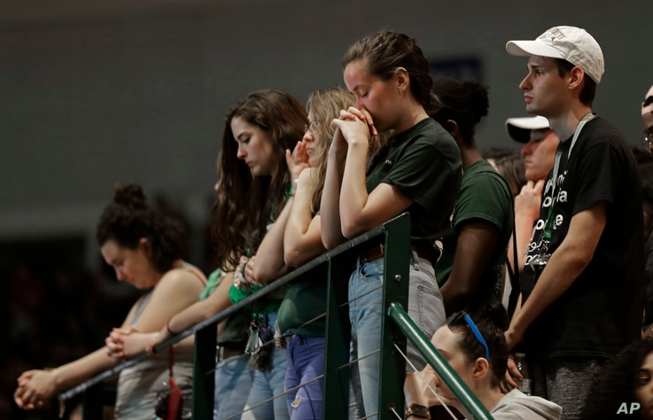 Students observer a moment of silence during a vigil at the University of North Carolina-Charlotte in Charlotte, N.C., May 1, 2019 after a student with a pistol killed two people and wounded four others on Tuesday.